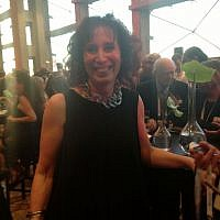 NYer Jo-Ann Mort in a drapy black tank dress and chunky chain (photo credit: Sarah Tuttle-Singer/Times of Israel)