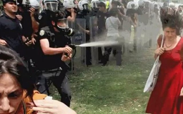 The policeman fires tear gas directly at the woman in the red dress from close range (YouTube screenshot)