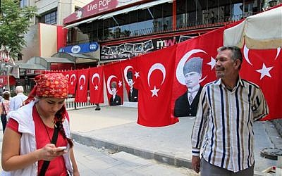 A street vendor seen with his national flags and posters of Turkey's founder Kemal Ataturk, in Kizilay Square, in the main city center of Ankara,Turkey, Wednesday, June 5, 2013 (photo credit: AP/Burhan Ozbilici)