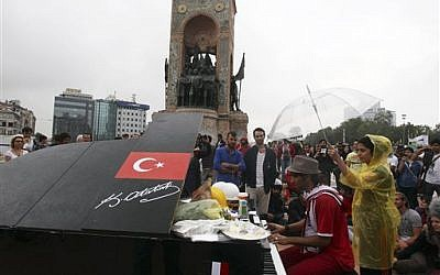 A musician plays the piano under the monument of Mustafa Kemal Ataturk, founder of the modern Turkey, at Taksim Square in Istanbul Friday, June 14, 2013 (photo credit: AP Photo/Thanassis Stavrakis)