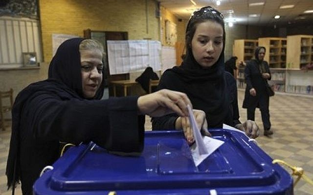 Illustrative photo of two Iranian women casting their ballots during the presidential and municipal councils elections in a polling station in Tehran, Iran, Friday, June 14, 2013 (AP Photo/Vahid Salemi)