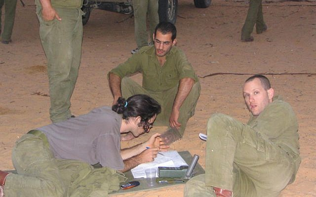 Kali, right, with two soldiers from the platoon, preparing a navigational route (Photo credit: Courtesy: Gal Kali)