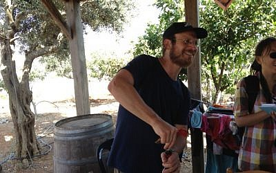 Eli Greenberg, uncorking a bottle at a local winery in Amona (Photo credit: Mitch Ginsburg/ Times of Israel)