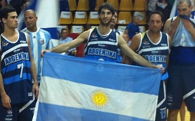 Andres Berman holds the Argentinian flag after finishing in second place (photo credit: Aaron Kalman)