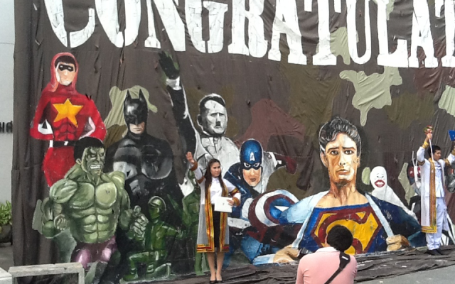 Passersby performing the Nazi salute in front of a mural  depicting Adolf Hitler alongside assorted superheroes in Thailand's Chulalong University (photo credit: Courtesy/Simon Wiesenthal center)