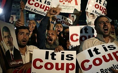 Supporters of Egypt's ousted president Mohammed Morsi chant slogans against members of the country's interim government in Cairo, Egypt, last week. (photo credit: AP/Hassan Ammar)