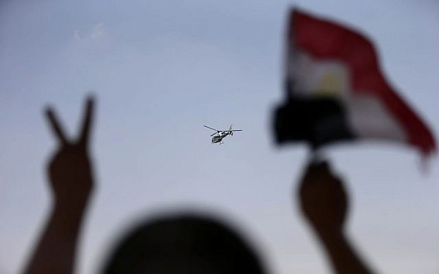 A police helicopter flies over the presidential palace, as a man waves the Egyptian national flag , in Cairo, Egypt, Tuesday, July 2 (photo credit: AP/Hassan Ammar)
