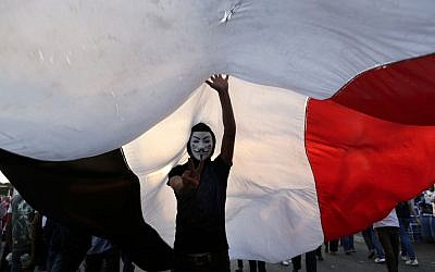 An opponent of Egypt's Islamist President Mohammed Morsi wearing a Guy Fawkes mask flashes the victory sign under a large Egyptian national flag during a protest outside the presidential palace, in Cairo, Egypt, Tuesday, July 2 (photo credit: AP/Hassan Ammar)