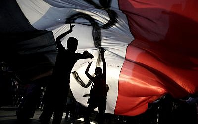 Opponents of Egypt's Islamist President Mohammed Morsi hold a large Egyptian national flag during a protest outside the presidential palace, in Cairo, Egypt, Tuesday, July 2, 2013 (photo credit: AP/Hassan Ammar)