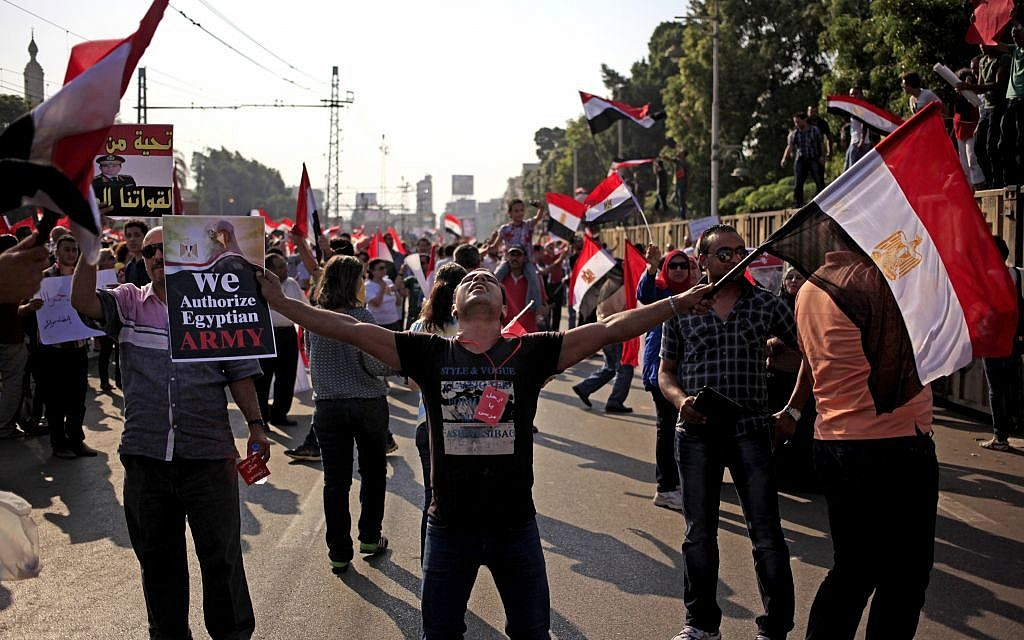 Opponents of Egypt's Islamist President Mohammed Morsi wave national flags during a protest outside the presidential palace on Wednesday. (Photo credit: AP/Khalil Hamra)