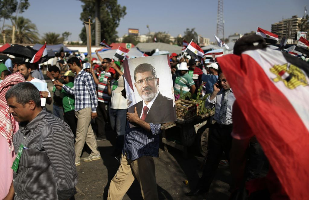 A supporter of Egypt's Islamist President Mohammed Morsi carries a photo of him during a rally, in Nasser City, Cairo, Egypt, Wednesday, July 3, 2013. (photo credit: AP/Hassan Ammar)