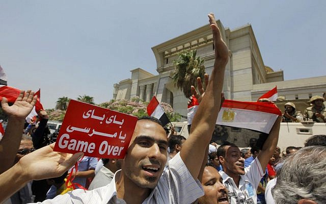 """Egyptians celebrate after Egypt's chief justice Adly Mansour is sworn in as the nation's interim president on Thursday, July 4, 2013. Arabic reads, """" bye bye Morsi."""" (photo credit: AP Photo/Amr Nabil)"""