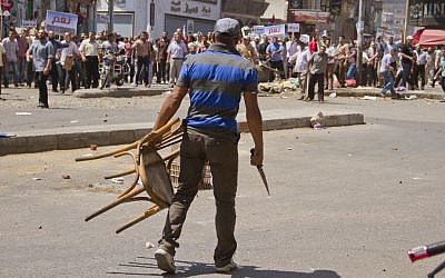 An Egyptian opposition protester holds a chair and knife during a clash between supporters and opponents of President Mohammed Morsi in downtown Damietta, Egypt, Wednesday, July 3, 2013 (photo credit: AP/Hamada Elrasam)