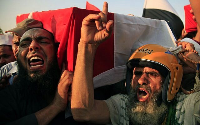 Supporters of Egypt's ousted President Mohammed Morsi chant angry slogans as they carry a coffin covered with the national flag, of a man killed after Egyptian troops opened fire on mostly Islamist protesters marching on a Republican Guard headquarters Friday, in Cairo, Saturday, July 6, 2013 (photo credit: AP/Khalil Hamra)