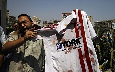 A supporter of ousted Egyptian President Mohammed Morsi stands outside a local hospital in Cairo holding a bloodied shirt he says belongs to a protester shot by soldiers during a demonstration, Monday, July 8, 2013 (photo credit: AP/Nasser Shiyoukhi)