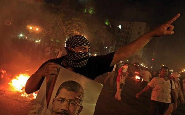 A supporter of ousted President Mohammed Morsi holds a poster of him during clashes in downtown Cairo, Egypt, on Monday, July 15, 2013. (photo credit: AP Photo/Khalil Hamra)