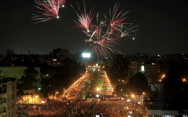 Fireworks light the sky as opponents of Egypt's Islamist President Mohammed Morsi protest outside the presidential palace in Cairo, Egypt, Monday, July 1 (photo credit: AP/Khalil Hamra)