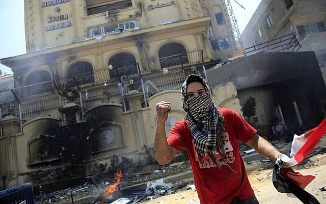 A protester holds an Egyptian national flag as he and others attack the Muslim Brotherhood headquarters in the Muqattam district in Cairo, Monday, July 1, 2013 (AP Photo/Khalil Hamra)