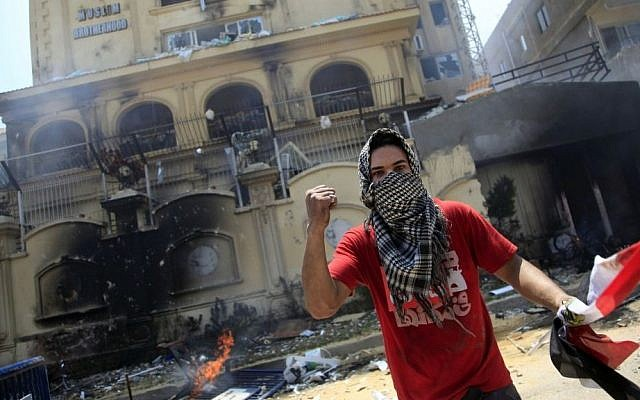 A protester holds an Egyptian flag as he and others attack the headquarters of the Muslim Brotherhood in the Muqattam district of Cairo, Egypt, earlier this month. (photo credit: AP/Khalil Hamra)