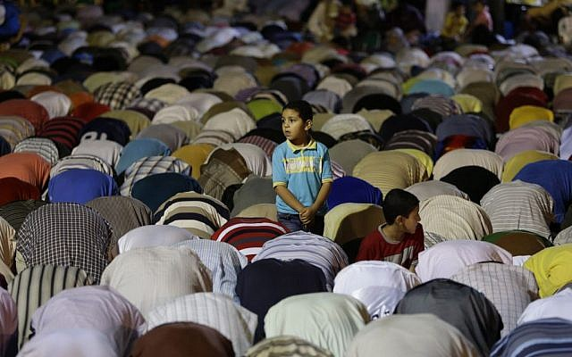 An Egyptian boy stands among the supporters of ousted Egypt's President Mohammed Morsi during evening prayer in Cairo on July 10, 2013. (photo credit: Hussein Malla/AP)