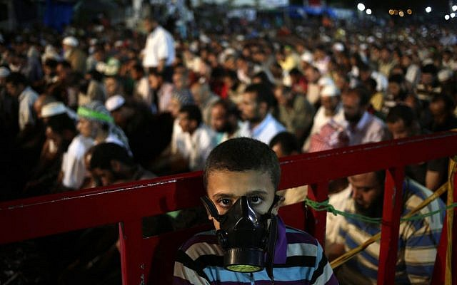 A boy wears a tear gas mask as supporters of Egypt's ousted resident Mohammed Morsi pray at Nasr City, in Cairo on July 28, 2013. (photo credit: Hassan Ammar/AP)