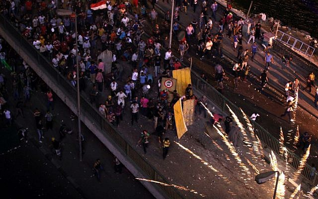 Supporters and opponents of Egypt's ousted Islamist President Mohammed Morsi clash on the 6 October bridge, near Maspero, where Egypt's state TV and radio station is located, in Cairo, Egypt, Friday, July 5, 2013. (Photo credit: AP/Khalil Hamra)