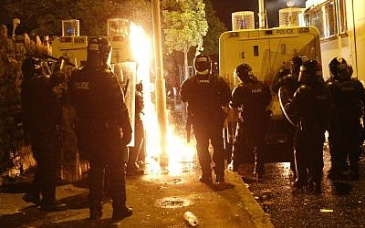 Riot police watch flames of Molotov cocktails thrown by Protestant hardliners in North Belfast, Northern Ireland, early Saturday. (photo credit: AP/Peter Morrison)