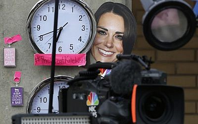 A mask depicting Britain's Duchess of Cambridge and clocks showing New York and London time, placed by members of the media, are seen across from St. Mary's Hospital exclusive Lindo Wing in London, Sunday, July 21, 2013. (photo credit: AP/Lefteris Pitarakis)