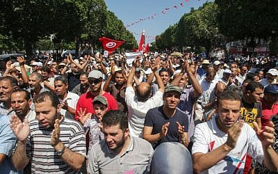 Supporters of the Islamist Ennahda movement march in the streets of Tunis during a demonstration to condemn the assassination of politician Mohammed Brahmi in Tunisia, Friday, July 26, 2013. (photo credit: AP/Amine Landoulsi)