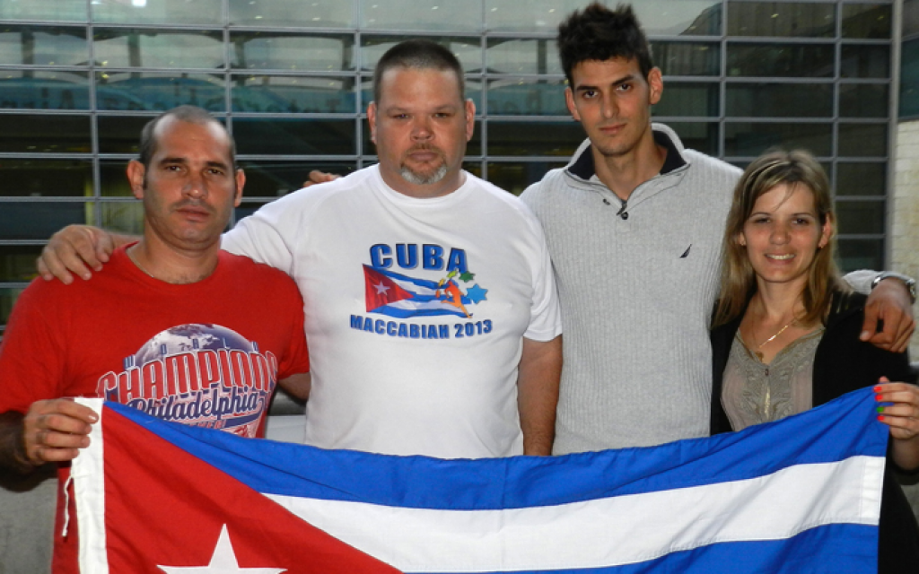 Cuban softball player Alberto Tacher, left, and coach Roberto Saria Popowsky, both living in Israel, welcome archery siblings and fellow Cuba natives Rafael, second from right, and Roxana Gonzalez upon their arrival at Ben Gurion Airport to participate in the Maccabiah Games, July 3, 2013. (photo credit: Facebook/JTA)
