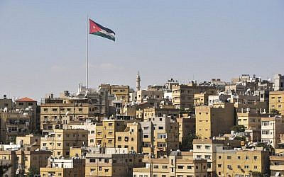 A view of Amman, with the Jordanian flag flying high over the city (photo credit: Michal Shmulovich/Times of Israel)