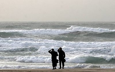 Two ultra-Orthodox men look at the stormy sea on a beach in Ashdod (photo credit: Edi Israel/Flash90)