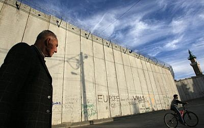 A Palestinian man walks past the Israeli security barrier in the East Jerusalem village of Abu Dis (Kobi Gideon/Flash90)