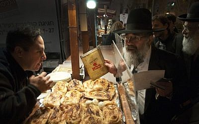 Illustrative photo of a representative of Israel's Chief Rabbinate inspecting a suspicious kosher certificate at a food stand in Jerusalem (photo credit: Rubin Salvadori/Flash90/File)