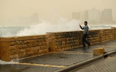 A man photographs the waves hitting the shore of the Jaffa port on a stormy day (illustrative photo credit: Tomer Neuberg/Flash90)