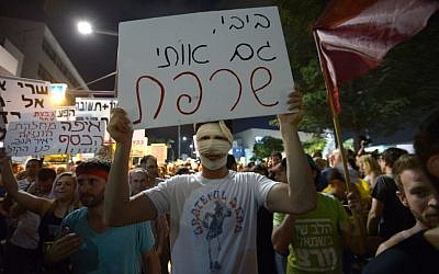 "Protesters returned to Tel Aviv on Saturday night. This protester's sign reads 'Bibi, you have burned me too,"" a reference to budget cuts and Moshe Silman, who self-immolated one year ago. (photo credit: Gili Yaari/ Flash90)"