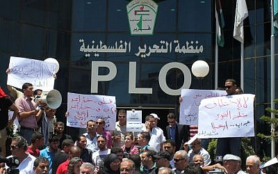 Palestinians demonstrate in front of the Palestine Liberation Organization offices in the West Bank city of Ramallah, on July 15, as they protest against secret meetings between officials from the PLO and Israel. (photo credit: Issam Rimawi/FLASH90)