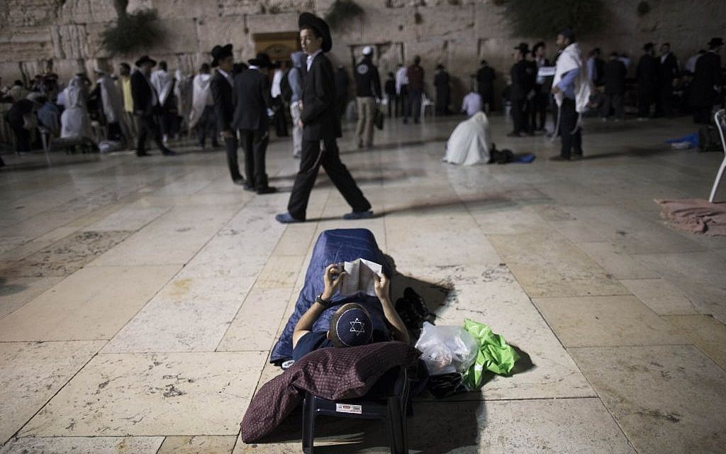 A man laying down as he recites Lamentations on the ninth of Av, at the Western Wall (photo credit: Yonatan Sindel/Flash 90)