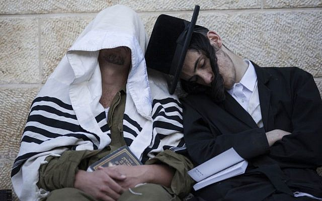 An ultra-Orthodox Jewish man falls asleep on an Israeli soldier during the ritual prayer of Tisha B'Av at the Wall Western in the Old City of Jerusalem, on July 16, 2013. (photo credit: Yonatan Sindel/Flash90)