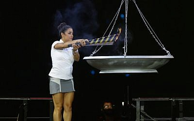 US Olympic gymnast Aly Raisman lights the torch at the opening ceremony of the Maccabiah Games in Jerusalem, Israel, on Thursday (photo credit: Yonatan Sindel/Flash90)