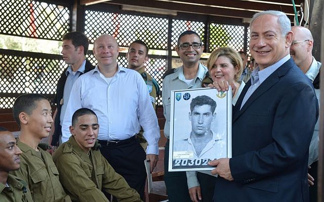 On a visit to new IDF recruits, Prime Minister Netanyahu holds up a picture from when he was drafted. (photo credit: Yossi Zeliger/Flash90)