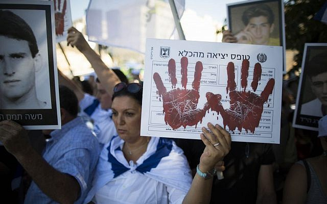 Relatives of Israelis killed in terror attacks demonstrate ahead of the cabinet vote to free 104 Palestinian prisoners, outside the Prime Minister's Office, in Jerusalem in August. The poster reads 'Prisoner release form.' (photo credit: Yonatan Sindel/Flash90)