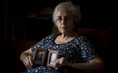 Cati Holland holds photos of her grandparents at her house in the Israeli city of Hadera, Thursday, July 25, 2013. (photo credt: AP/Oded Balilty)