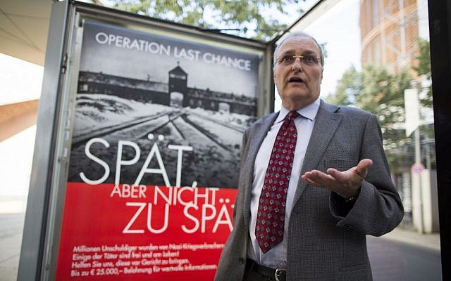 Efraim Zuroff, the top Nazi-hunter of the Simon Wiesenthal Center, talks to journalists as he stands in front of a placard reading 'Operation last chance - late but not too late' displayed in Berlin, Germany, Tuesday, July 23, 2013. (AP Photo/Gero Breloer)