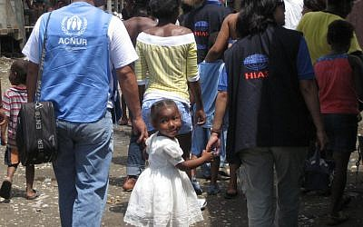 A young girl in Ecuador holding hands with representatives of HIAS, right, and the refugee agency of the United Nations. (photo credit: Courtesy HIAS/JTA)