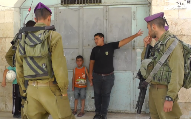 A Palestinian teenager tells IDF soldiers where the parents of 5-year-old Wadi' Maswadeh live. The boy was suspected of throwing stones at Israeli cars. (photo credit: screenshot/YouTube)