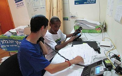 Two young volunteers man the phones. (photo credit: Debra Kamin/Times of Israel)