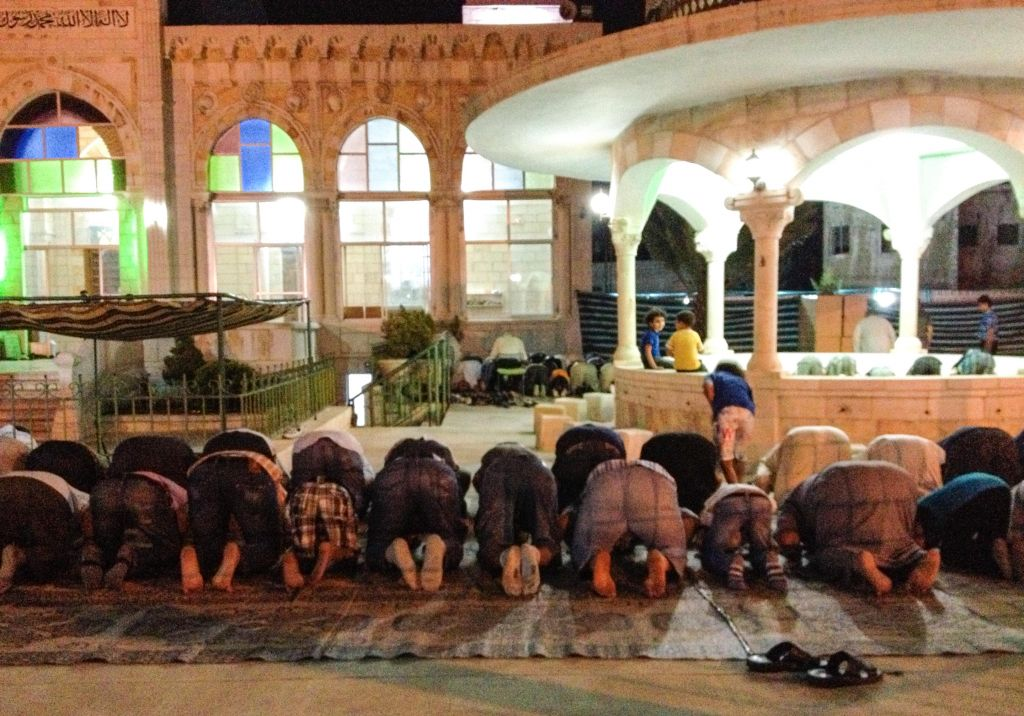 Men engage in communal prayer outside a mosque just before 8 pm, at which time the fast of Ramadan is broken in Amman (photo credit: Michal Shmulovich/Times of Israel)