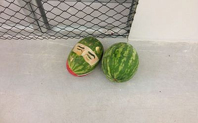 "Fine arts student Iftach Ayali paints faces on watermelon in his work ""Yes"" (photo credit: Nicole Levin/Times of Israel)"
