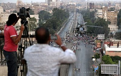 Journalists film an Egyptian military attack helicopter flying by the Presidential palace, in Cairo, Egypt on Friday, July 5 (photo credit: AP/Hassan Ammar)